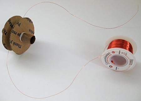 Magnet wire from a spool is wrapped around a spool made from paper and cardboard