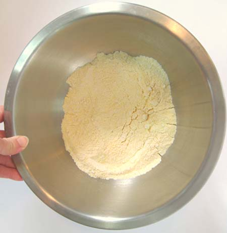 A mixing bowl with the dry ingredients for corn muffins.