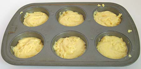 Muffin batter in cups on a pan.