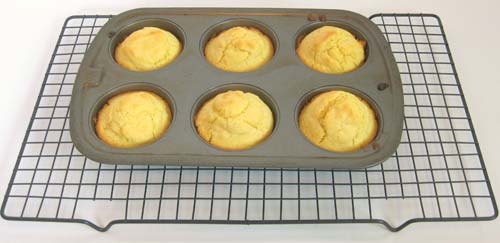 Baked muffins in a pan on a cooling rack