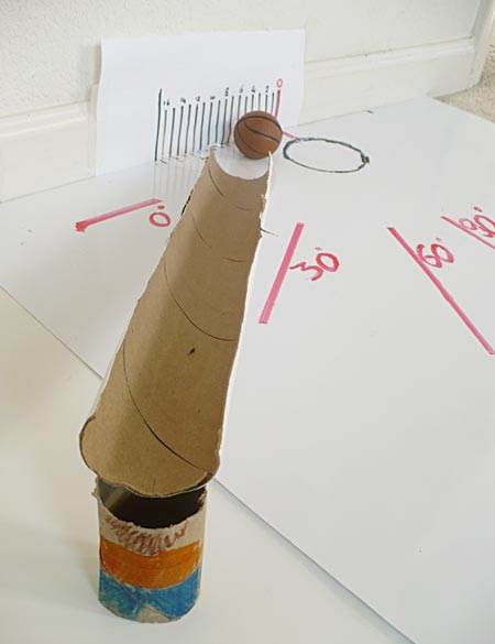 A cut-open cardboard tube guides the ball toward the scale model backboard.