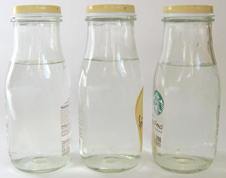 Three glass bottles are filled with an equal amount of water