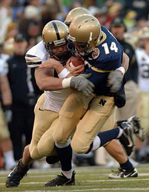 Photo of a football player being tackled on the field
