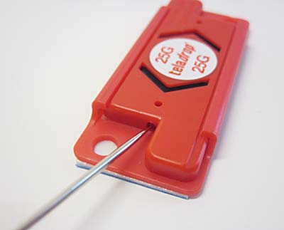 A needle is used to reset an activated shock indicator