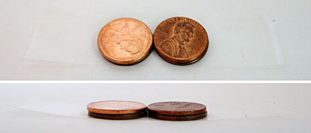 Two stacks of two pennies lay on a piece of tape next to each other