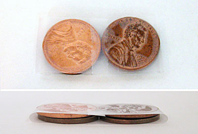 Two stacks of two pennies are wrapped in tape