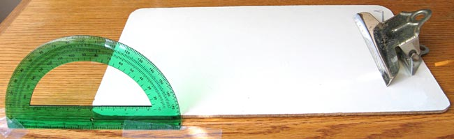 A protractor is taped perpendicular to a tables surface and aligned with a clipboards edge at the focal point