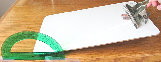 A stack of two pennies sitting on a paper towel strip are placed on a clipboard as the clipboard is raised at an angle