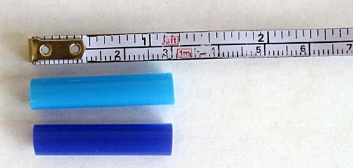 Two 3 cm-long straw pieces next to a tape measure