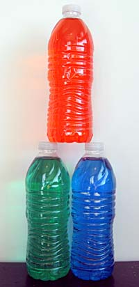Bottles with colored water arranged in a pyramid shape.