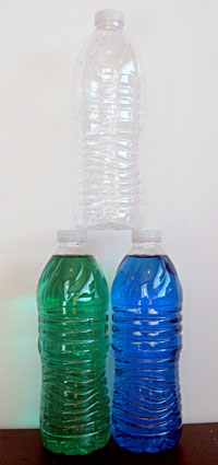 Bottles with colored water arranged in a pyramid shape, with two bottles filled on the bottom.