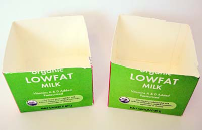 The bottom half of two cardboard milk cartons side by side