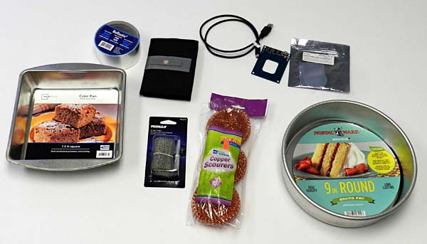 Aluminum tape, wire mesh and cake pan next to a steel pan, copper scrubbers, RFID shield, usb cable and RFID reader kit