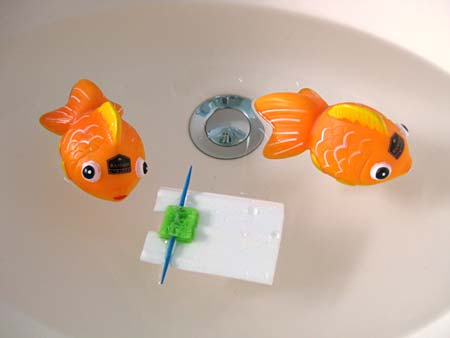 Two toy goldfish and a small white raft float in a pool of water
