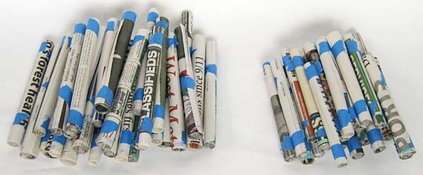 Two piles of newspaper tubes of different lengths