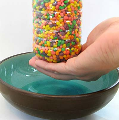 Bottle of Nerds candy above a bowl.