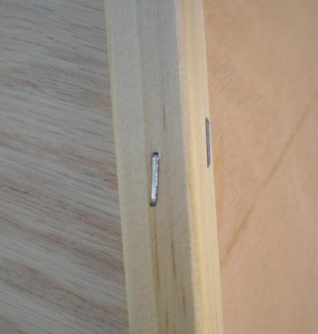 Close up photo of wooden corner guards stapled to a corner