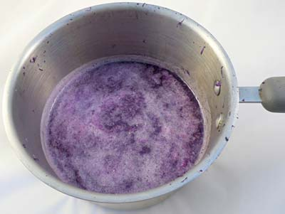 Grated purple cabbage soaking in a pot of boiling water