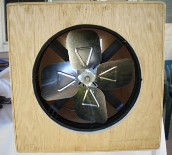 A fan rests in a circular hole cut from the center of a square wooden panel