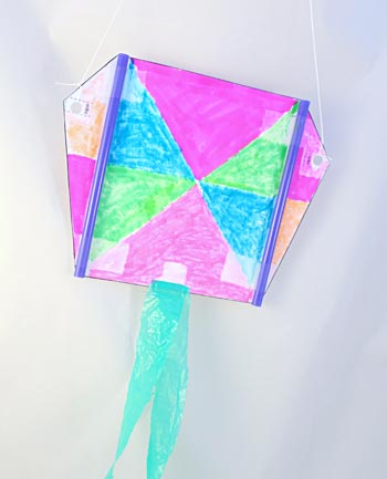 Homemade sled kite with plastic bag tails and crayon decorations.