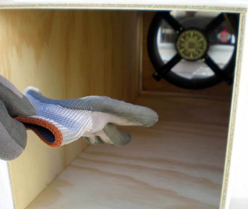Photo of a glove being pulled towards a fan at the end of a wooden box