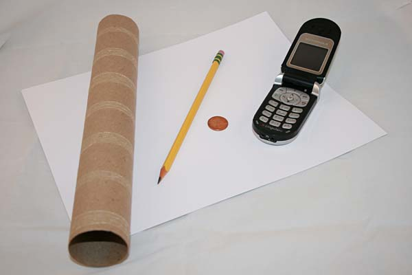 Materials needed to do a science activity determining dominant handedness and sidedness using paper, pencil, phone, tube, and penny.