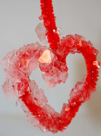 Borax crystals grown in the shape of a heart around a red pipe cleaner.