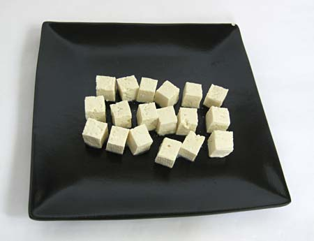 Black plate with 18 tofu cubes.