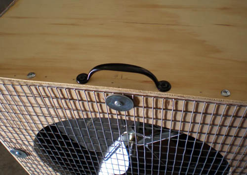 A handle is attached on the top side of a diffuser box above the fan