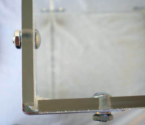 Screws and nuts are used to attach a corner bracket to the walls of a Plexiglas box