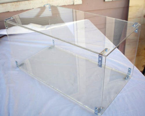 A rectangular prism made of Plexiglas is held together with silicone and corner brackets