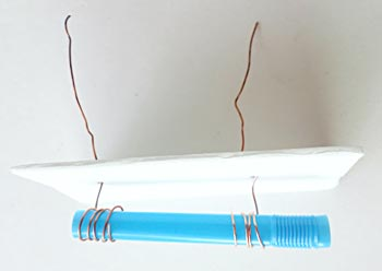 Blue straw connected to copper wire and going through Styrofoam to make a sensor.