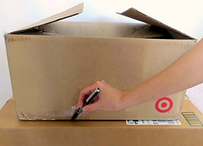 The outline of a smaller cardboard box is traced on the lid of a larger cardboard box