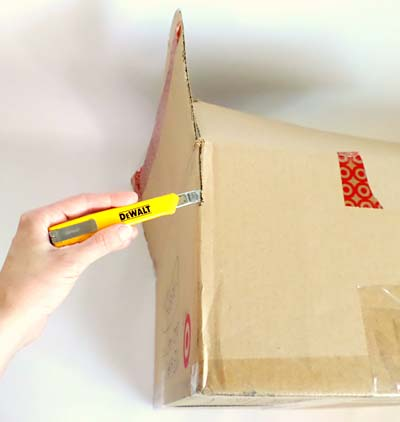The edge of a cardboard box where two walls meet is cut with a utility knife