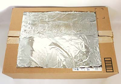 The inside of a cardboard box is lined with aluminum foil