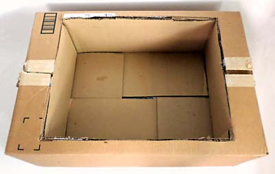 A smaller cardboard box is inserted into an opening in the lid of a larger cardboard box