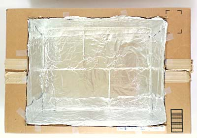 Aluminum foil lines the inside of a cardboard box that is sitting in a larger cardboard box