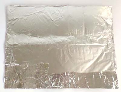 A rectangular piece of cardboard is wrapped in aluminum foil