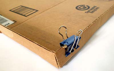 Binder clips are used to hold the corners of a cardboard lid together