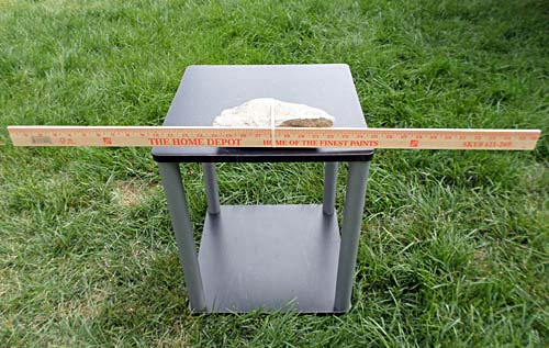 On a small table a meterstick is placed parallel to the ground and secured to a large rock
