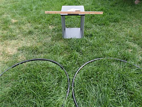 A table with a rock and yardstick on it sits in front of two hula hoops laying on the ground