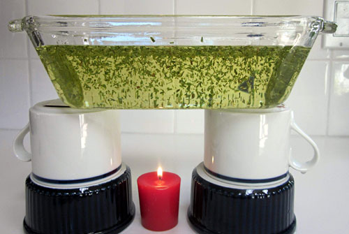 A lit candle sits under a glass dish filled with oil and dried thyme that is held up by two upside down cups