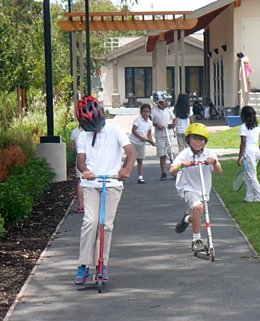 Children riding scooters on a sidewalk