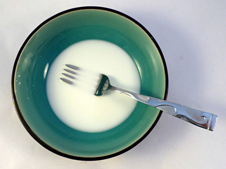 Cornstarch and water are mixed in a bowl with a fork