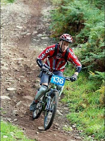 A bike rider going down dirt path