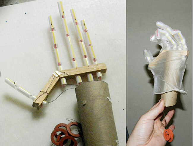 A homemade prosthetic hand made from straw, springs, strings, wood and cardboard