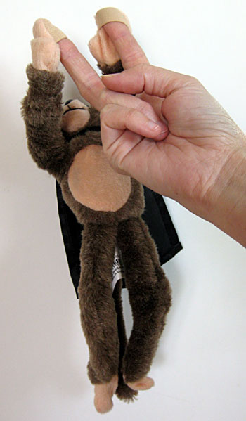 Two fingers attach to the hands of a stuffed toy monkey
