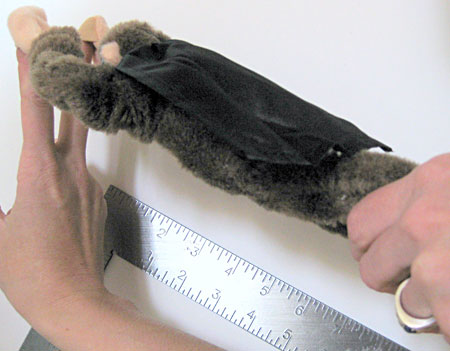 Stuffed toy monkey is held parallel to the edge of a carpenters square