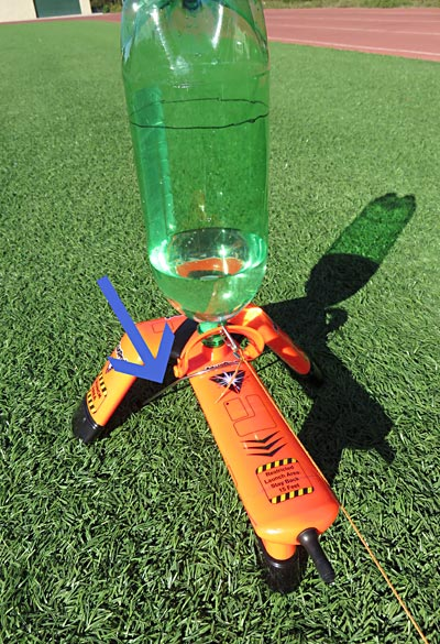 The bottle rocket launcher is held in place by a U peg going over the launcher and pushed into the ground.