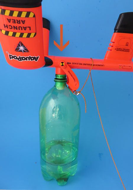 Placing the bottle rocket on the ground and pushing the launcher upside down in the bottle spout allows you to attach the rocket without spilling any water.